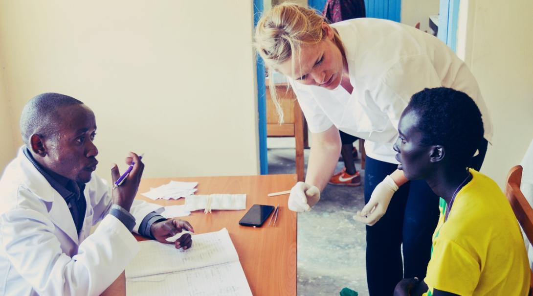 ケニアの診療所で患者の診察に対応する医師をサポートする医療インターン